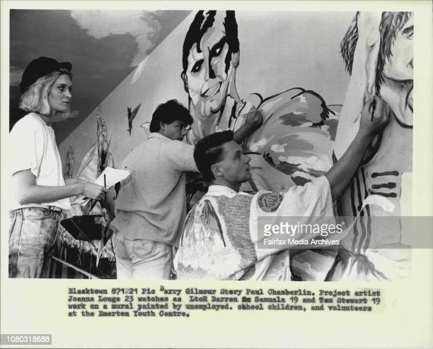 Project artist Joanna Louge 23 watches as L to R Darren Samuala 19 and Tom Stewart 19 work on a mural painted by unemployed School children and...