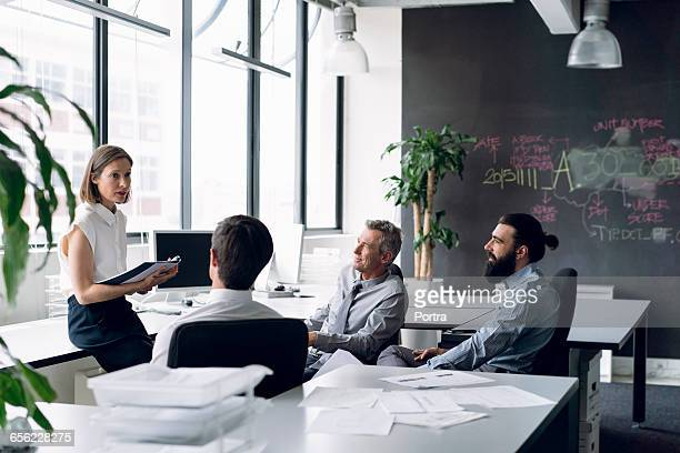Project manager communicating with male coworkers