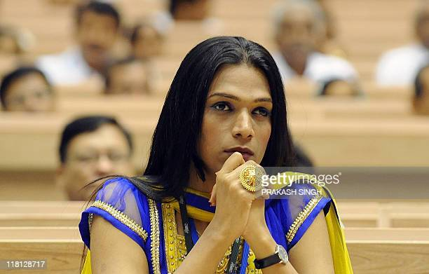 Project manager for the India HIV AIDS Alliance Abhina Aher from the Hijra community listens to Indian Prime Minister Manmohan Singh speak during the...