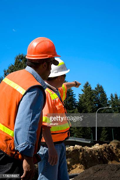 Project Manager overseeing Erosion control 'series' safety orange helmet pointing