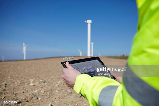 Project manager using digital tablet in front of wind farm