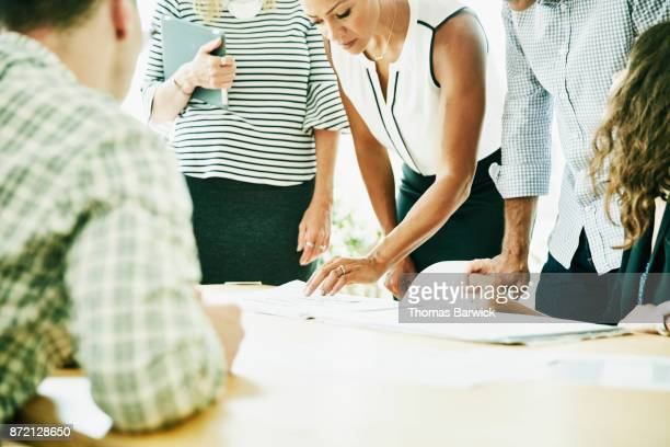 Project team examining plans on office conference table