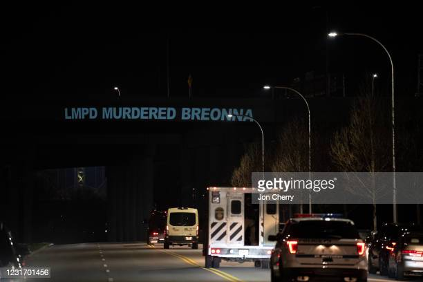 Projected phrase, LMPD MURDERED BREONNA, is seen on an overpass as Louisville Metro Police Department officers drive toward downtown on March 13,...