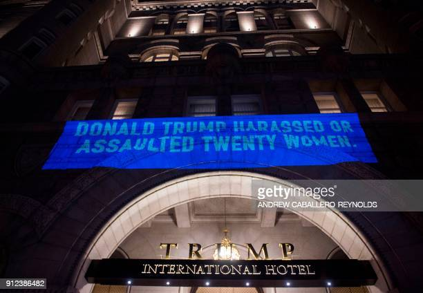 A projection by Artist Robin Bell is seen on the side of the Trump International Hotel in Washington DC on January 30 2018 / AFP PHOTO / Andrew...