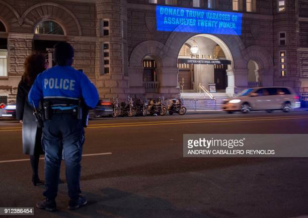 TOPSHOT A projection by Artist Robin Bell reading 'Donald Trump harassed or assaulted twenty women' is seen on the side of the Trump International...