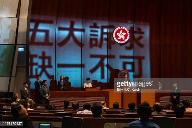 A projection reading 'Five demands not one less' is seen as Hong Kong's Chief Executive Carrie Lam gives her annual policy address at the Legislative...