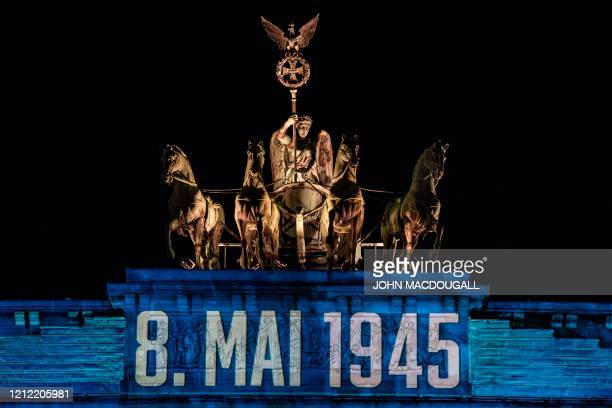 A projection reading thank You in Russian English French and German with 8 May 1945 projected just under the quadriga lights up Berlin's Brandenburg...