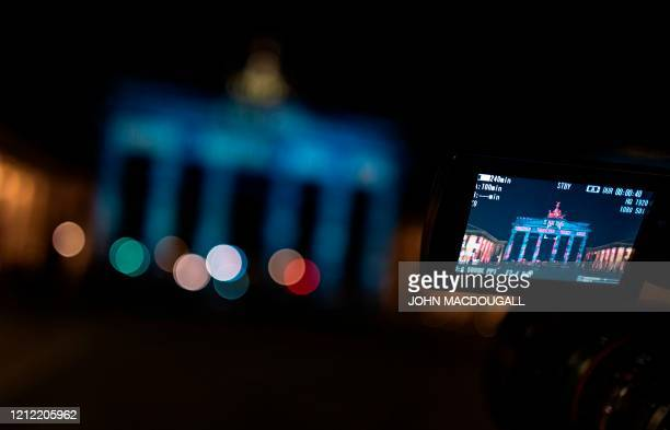 A projection reading thank You in Russian English French and German lighting up Berlin's Brandenburg Gate is seen through the screen of a video...