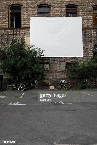 projection screen in empty car park at postfuhramt building - autokino stock-fotos und bilder