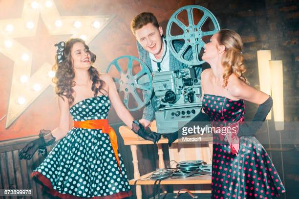 projectionist flirting with beautiful girls - divergent film stock photos and pictures