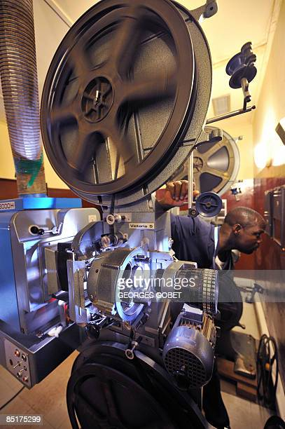 Projectionist Michel Dianda keeps watch over his 35mm projectors in the projection booth at the Burkina Cinema in Ouagadougou on March 2, 2009 where...
