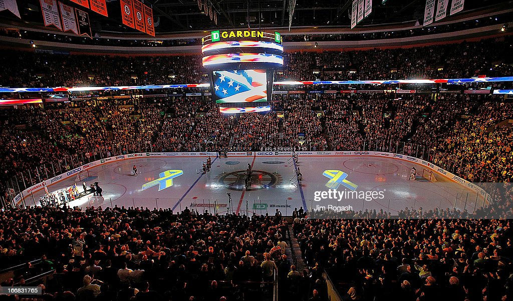 Projections of the Boston Marathon Memorial Ribbon are seen on the ice during pre-game ceremonies in remembrance of the Boston Marathon bombing victims before a game between the Buffalo Sabres and the Boston Bruins at TD Garden on April 17, 2013 in Boston, Massachusetts.