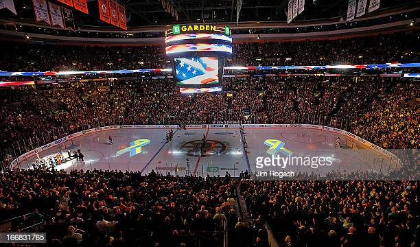 Projections of the Boston Marathon Memorial Ribbon are seen on the ice during pregame ceremonies in remembrance of the Boston Marathon bombing...