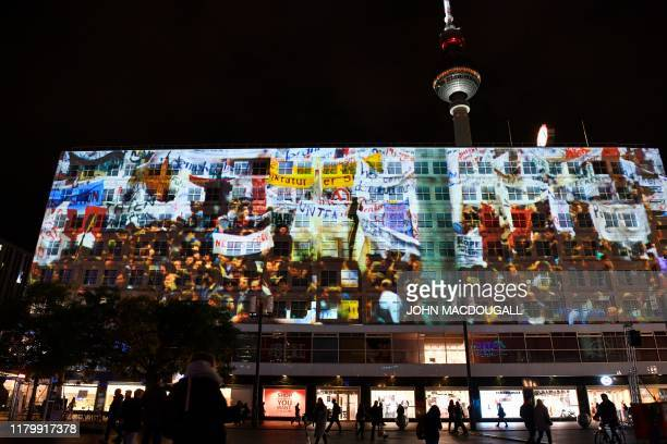 Projections on the buildings at Alexanderplatz next to the TV tower during the citywide kickoff of the festival week will to celebrate the 30th...