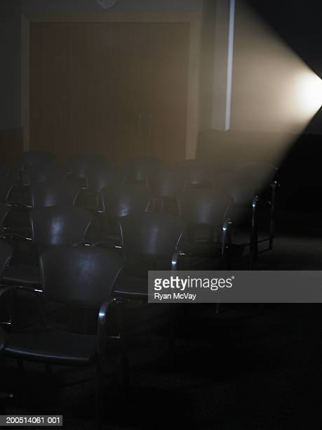 Projector casting light on rows of empty chairs in conference room