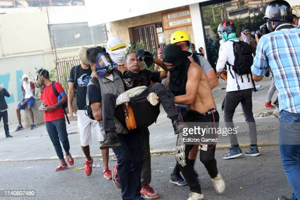 A proJuan Guaidó demonstrator receives help after being injured in a conflict against police forces after the May 1 demonstration near Plaza Altamira...