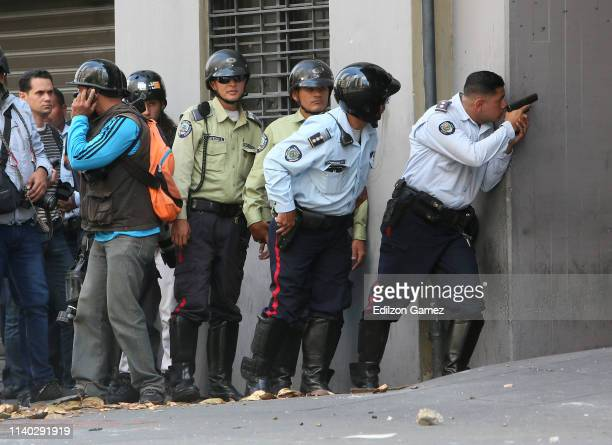 ProJuan Guaido military police officers confront ProGovernment armed civilians inside the Ministry of Housing at Avenida Francisco de Miranda on...