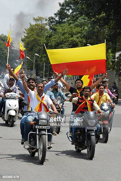 ProKarnataka activists wave the Karnataka flag while they participate in a motorcycle rally during a statewide strike in Bangalore on September 9...