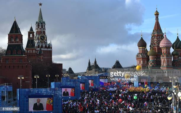 ProKremlin supporters attend a rally and a concert in central Moscow with the Kremlin's Spasskaya Tower and St Basil's Cathedral seen in the...