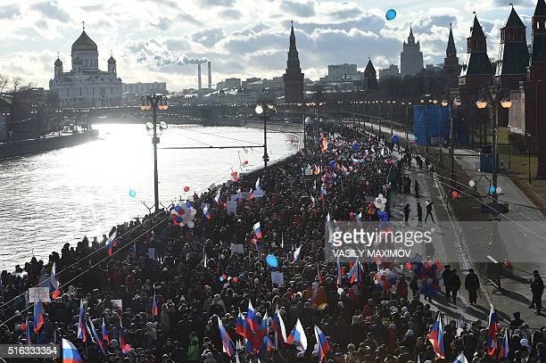 ProKremlin supporters march during a rally in central Moscow with the Kremlin towers and the Cathedral of Christ the Saviour seen in the background...