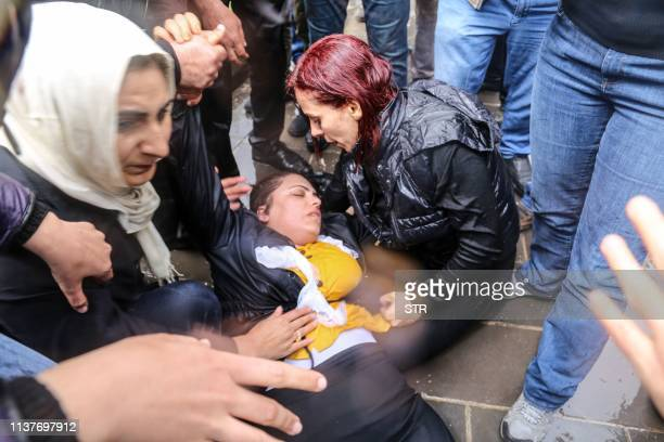 ProKurdish Peoples' Democratic Party lawmaker Remziye Tosun falls after being hit by a police water cannon during a protest against results of the...