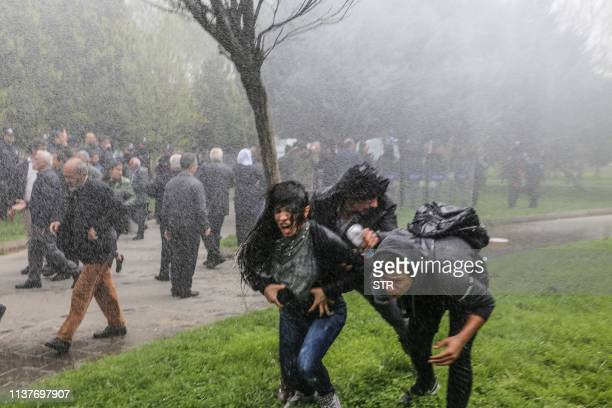 ProKurdish Peoples's Democratic Party members run after being hit by a police water cannon during a protest against results of the local elections in...
