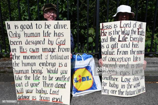 TOPSHOT Prolife activists hold up antiabortion religious messages on placards during a Stand up for Life rally calling for a 'no' vote in the...