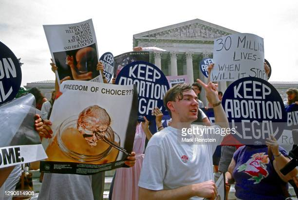 Pro-life and pro-choice demonstrators hold signs on the steps of the Supreme Court building The protests came after the court ruled on the Missouri...