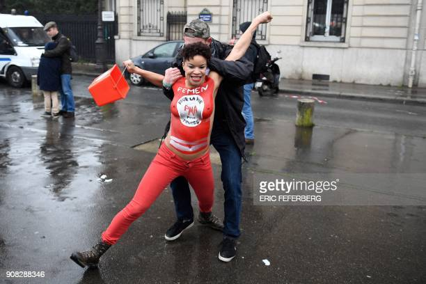 A prolife demonstrator grabs a member of feminist movement Femen group with lettering on her body reading 'medically assisted procreation for all' in...