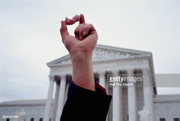 Pro-life demonstrator holds up a tiny plastic model of a fetus during an anti-abortion march in front of the Supreme Court in Washington, DC. On...