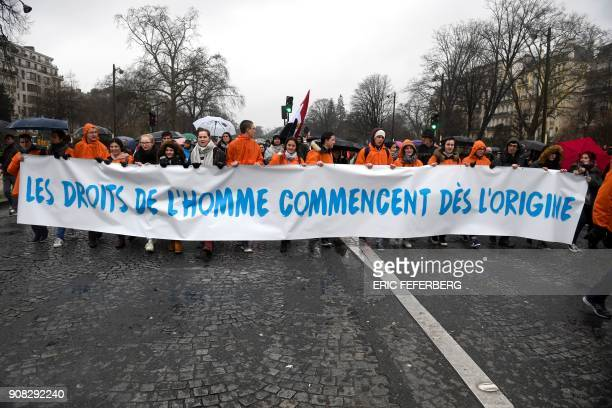 Prolife demonstrators hold banners reading 'Human rights begin from the origin' in Paris on January 21 2018 during a 'March for life' demonstration...