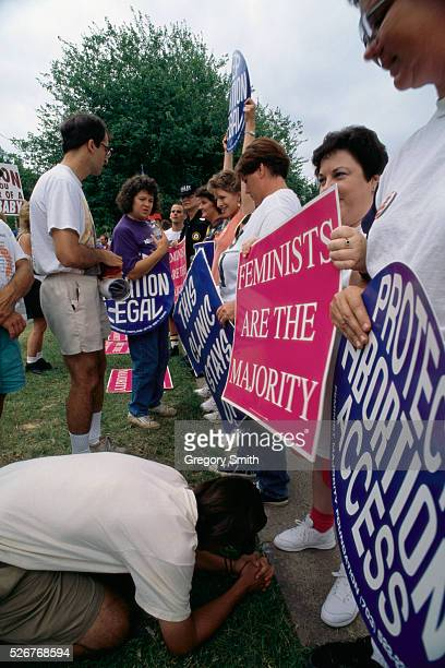 A prolife protester kneels at the foot of a prochoice protester and prays during a prochoice demonstration outside a pregnancy center in Little Rock...