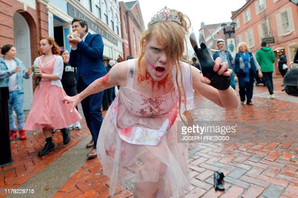TOPSHOT Prom queen Deanna Lehman walks the streets during Halloween on October 31 2019 in Salem Massachusetts Salem is a mecca for witches and fans...