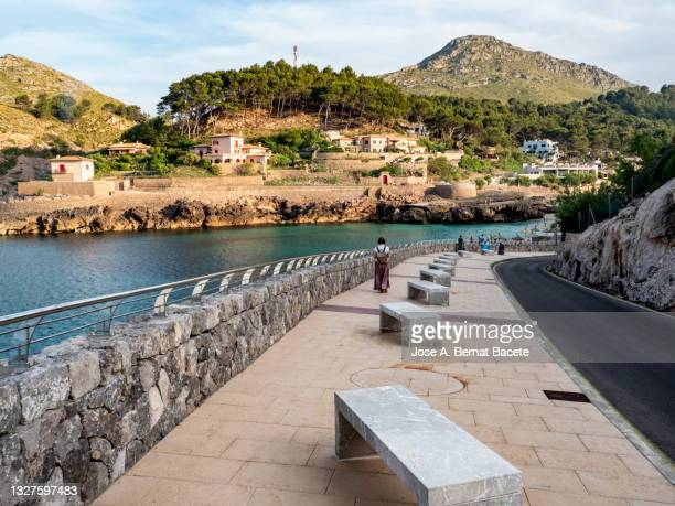 promenade along the sea at sunset in cala sant vicenç, majorca island. - sea swimming stock pictures, royalty-free photos & images