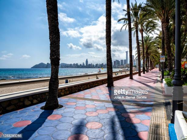 promenade and beach  against blue sky on the poniente beach in benidorm, spain. - beach sunbathing spain stock pictures, royalty-free photos & images