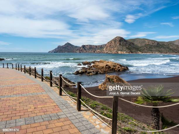 Promenade and beach with volcanic rocks and sand with the waves in movement.