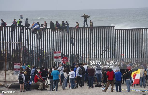 TOPSHOT Promigrant caravan demonstrators climb the USMexico border fence during a rally on April 29 in San Ysidro California The US has threatened to...