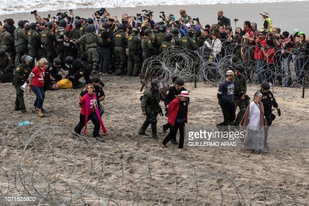 TOPSHOT Promigrants activists are arrested as they demonstrate against US migration policies near the USMexico border fence at Imperial beach in San...