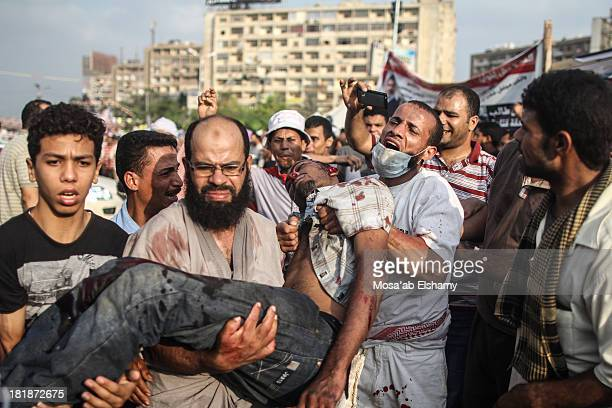 CONTENT] ProMorsi protesters carry away the body of a shut man during clashes with security forces outside Rabaa square