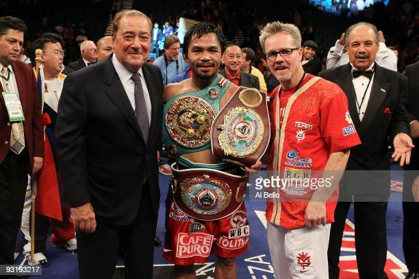 Promoter Bob Arum boxer Manny Pacquiao and trainer Freddie Roach celebrate Pacquiao's 12 round TKO victory against Miguel Cotto during their WBO...