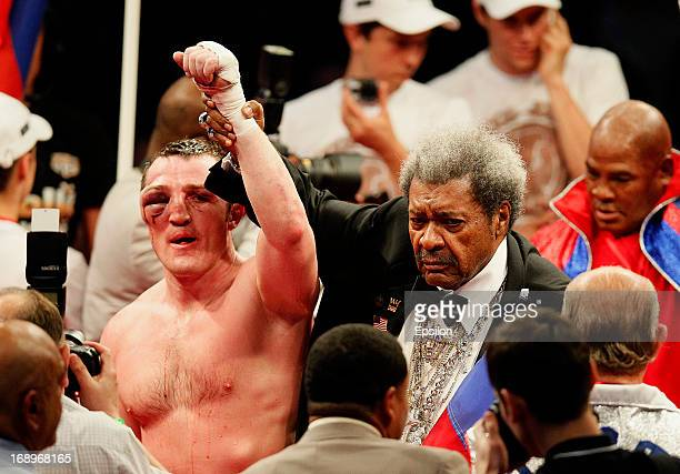 Promoter Don King lifts the arm of Denis Lebedev of Russia after he was defeated by Guillermo Jones of Panama during their WBA cruiserweight title...
