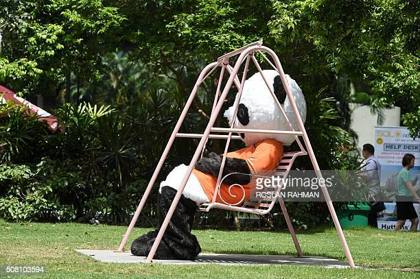 A promoter dressed in a panda outfit takes a break on a swing in the financial district of Raffles Place in Singapore on February 3 2016 Job...