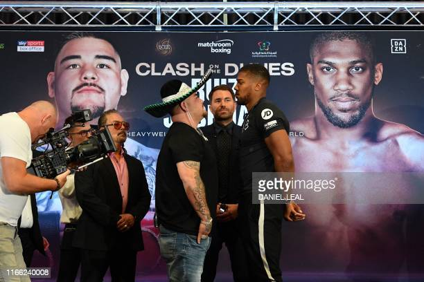 Promoter Eddie Hearn stands between MexicanUS WBA IBF WBO and IBO heavyweight boxing champion Andy Ruiz Jr and Britain's Anthony Joshua as they pose...