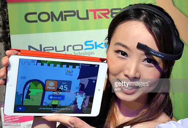 """Promoter wears a NeuroSky brainwave starter kit called """"MindWave Mobile"""" during a pre-show press conference for 2013 Computex Taipei show on May 28,..."""