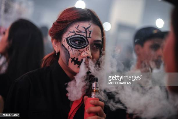 A promoter with a painted face smokes an electronic cigarette during the VapeFair in Kuala Lumpur on December 5 2015 Vaping is an alternative to...