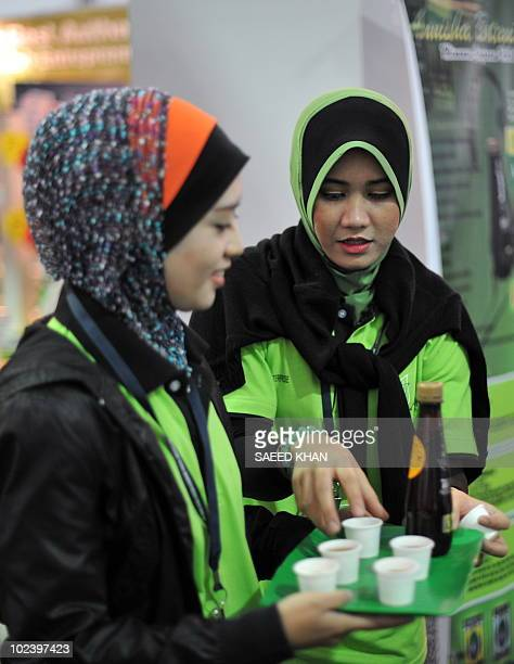 Promoters arrange samples of halal juice at an exhibition of halal products in Kuala Lumpur on June 25 2010 Malaysia is holding a five day...