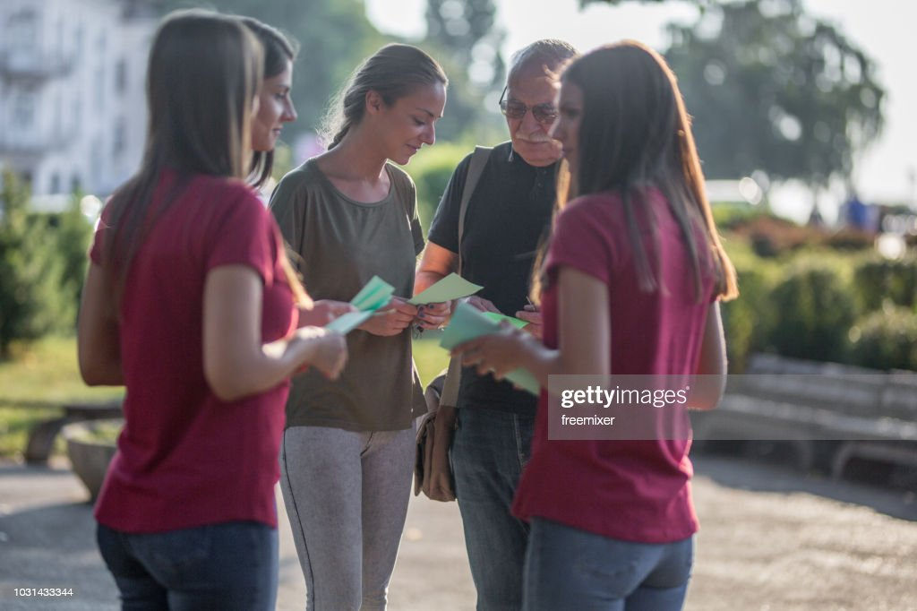 Promoters sharing flyers in the park : Stock Photo