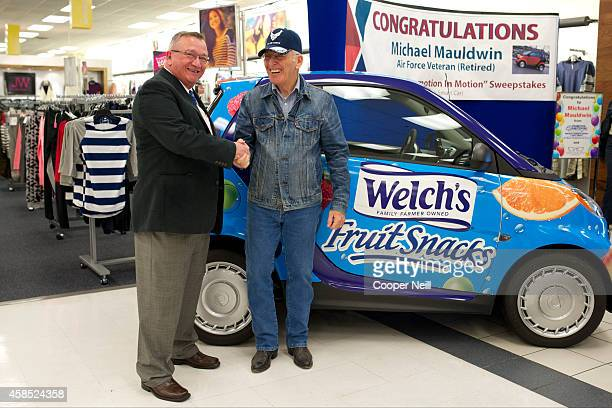 Promotion In Motion Vice President of Sales Jim Finelli shakes hands with Michael Mauldwin winner of a new Smart Car from the makers of Welch's Fruit...