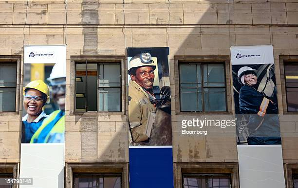Promotional banners with photographs of employees at work hang from the offices of Anglo American Plc stand in the Marshalltown district of...