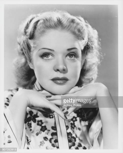 Promotional headshot of actress Alice Faye resting her chin on her hands circa 1935
